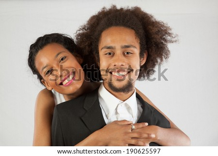 Cute Black couple together she is hugging him from behind and looking at the camera with a friendly, happy, smile