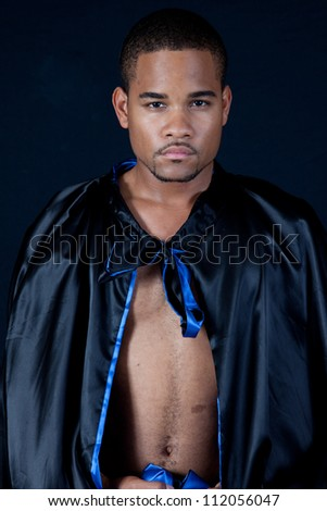 Cute black man with a black cape, looking right over the shiny material