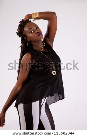 Cute black woman in black and white striped pants, with her hand across her head and looking into the camera with a serious expression - stock photo