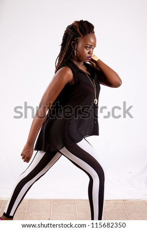Cute black woman in black and white striped pants, with her hand on her neck,  looking into the camera with a serious expression - stock photo