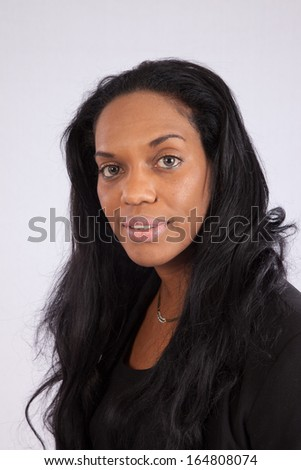 Cute Black woman with long black hair, looking at the camera with a pleased smile