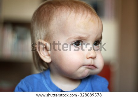 Cute blond baby boy with puffed-out cheek because of sugar candy, indoor portrait - stock photo