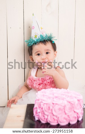 Cute blond baby girl in a pink tutu and ponytail sitting on a green background playing with icing in her hands from her double tier green pink and purple fondant iced heart birthday party cake - stock photo