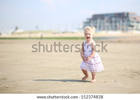 Cute blond baby girl in beautiful dress walking on a long sandy beach with apartment blocks at a background - stock photo