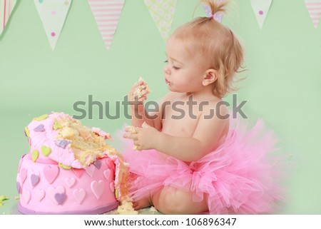Cute blond baby girl in pink tutu and ponytail sitting on green background by  birthday party double tier pink and purple fondant iced cake with hands in cake happy and excited to celebrate and eat it