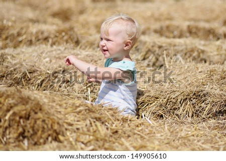 Cute blond baby girl playing with straw sitting inside a hay labyrinth during halloween celebrations  - stock photo