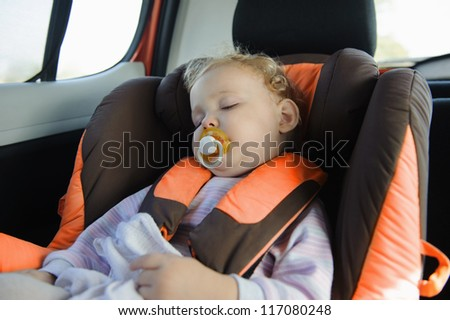 Cute blond baby sleeping peacefully in baby car seat - stock photo