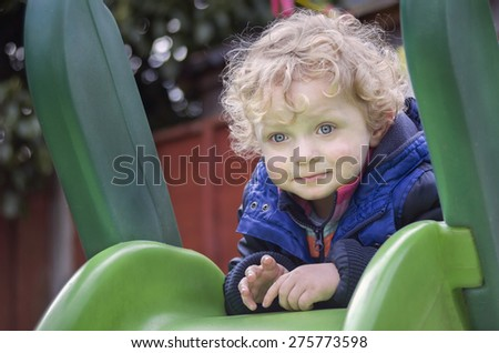 Cute Blond Boy  at the Playground in  early spring - stock photo