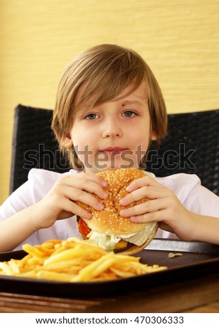 cute blond boy eating a hamburger and fries