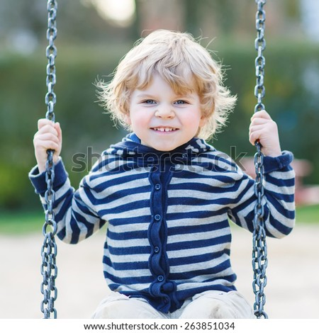 Cute blond boy having fun and swinging on outdoor playground. - stock photo