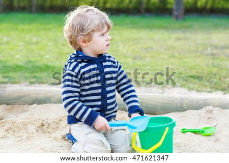 Cute blond boy having fun with sand on outdoor playground. Happy kid playing with toys on warm sunny day.