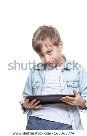 Cute blond boy in a blue shirt showing a tablet pc (isolated on white background)   - stock photo