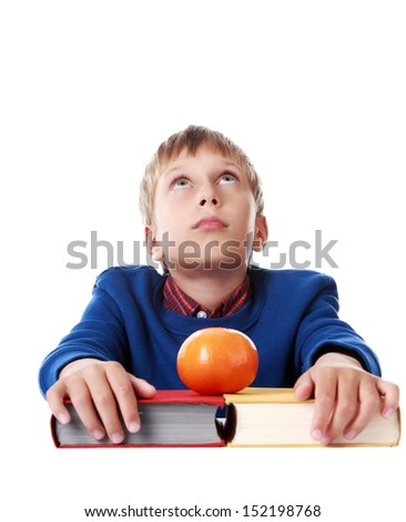 Cute blond boy in a blue sweater sitting with two colorful hardcover books and a tangerine looking upwards (isolated on white background)  - stock photo