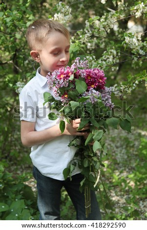Cute blond boy in a white shirt with a bouquet of flowers in the beautiful blossoming garden - stock photo