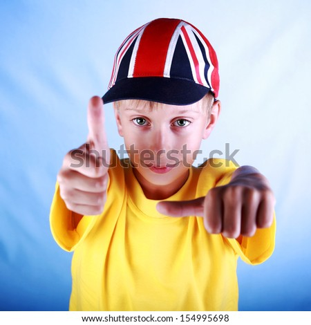 Cute blond boy in a yellow t-shirt wearing a baseball cap with a British national flag smiles happily showing thumbs up - stock photo