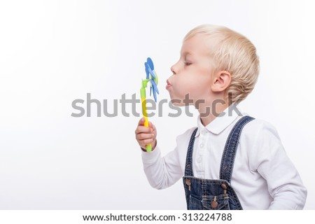 Cute blond boy is playing with a toy. He is holding a small pinwheel and blowing at it with efforts. The boy is looking at it happily. Isolated and copy space in left side - stock photo