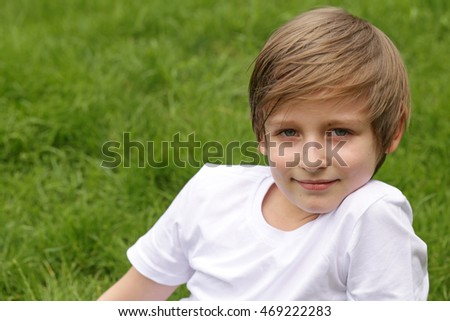 cute blond boy is sitting on green grass in the park