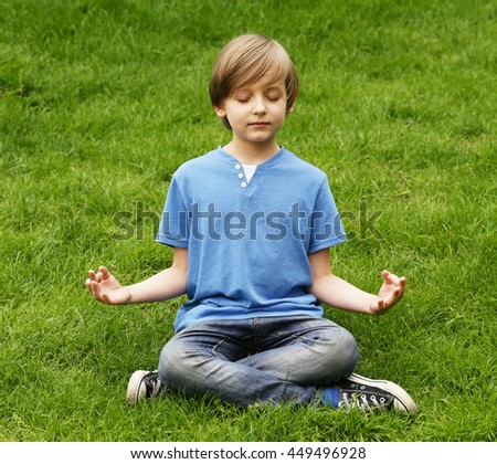 cute blond boy sitting on green grass and meditates - stock photo
