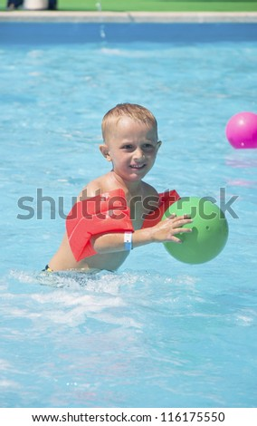 Cute blond boy with green ball in swimming pool - stock photo