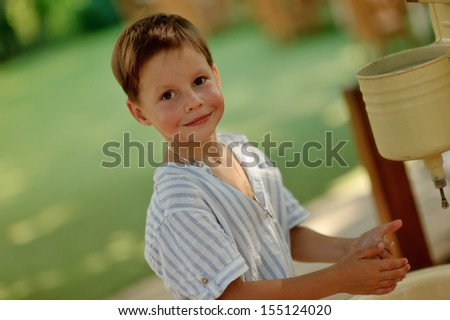 cute blond boy with rosy cheeks in a light shirt washes - stock photo
