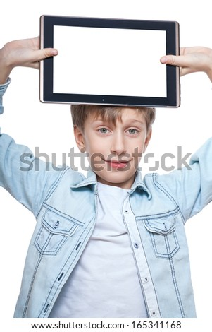 Cute blond child in a blue shirt holding tablet pc with white screen above his head smiling (isolated on white background)   - stock photo