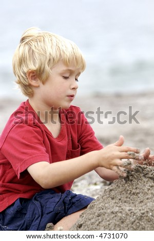 Cute blond child playing in the sand at the beach - stock photo