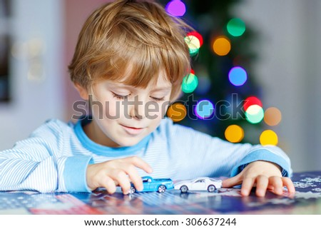 Cute blond child playing with cars and toys at home, indoor. funny boy having fun with gifts. Colorful christmas lights on background. Family, holiday, kids lifestyle concept. - stock photo