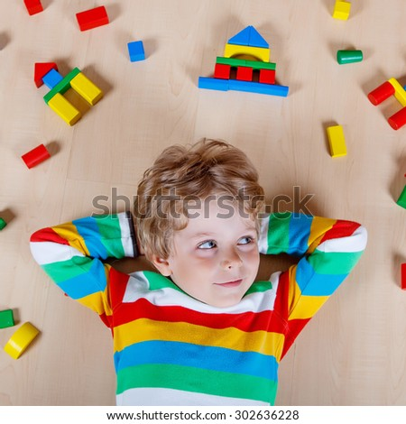 Cute blond child playing with lots of colorful wooden blocks indoor. Active kid boy wearing colorful shirt and having fun with building and creating. - stock photo