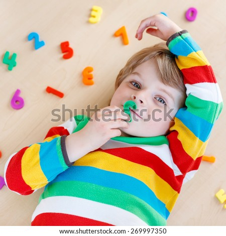 Cute blond funny kid boy playing with lots of colorful plastic digits or numbers, indoor. Child wearing colorful shirt and having fun with learning math - stock photo