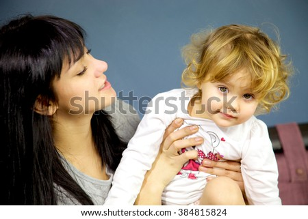 Cute blond girl laughing with young brunette mother