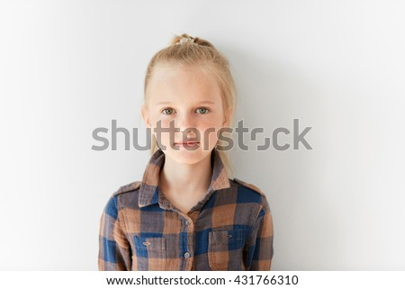 Cute blond girl posing on white background. Portrait of relaxed kid with nice kind look. Calm and pretty little Caucasian girl with pony-tail in brown shirt. Childish innocence, free and happy life. - stock photo