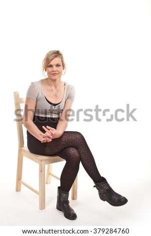 Cute blond girl sitting on a chiar and shot in studio with white background - stock photo