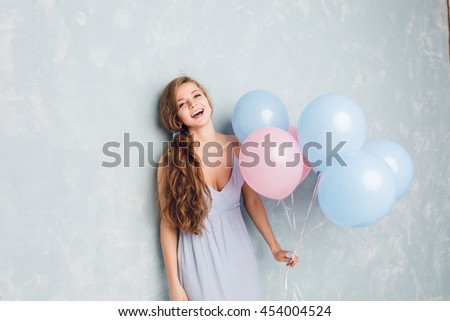 Cute blond girl standing in a studio, smiling and holding blue and pink balloons. She wears light blue, and has long braided and wavy hair with blue ribbon. - stock photo