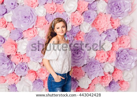 Cute blond girl stands and holds hands in her pockets smiling. She has long curly hair and wears blue jeans and white t-shirt off the shoulder. She has pink background covered in flowers. - stock photo