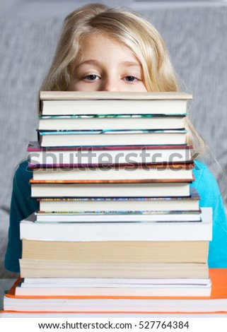 Cute blond girl with many books