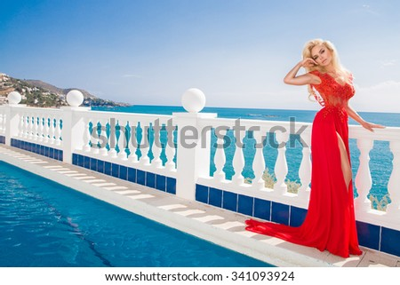 Cute blond hair sexy female model girl the pool in red elegant long dress with a long train with crystals background of blue sea in Santorini - stock photo