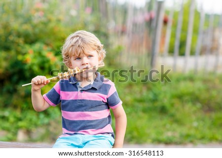 Cute blond kid boy eating waffle on straw - happy carefree childhood. Portrait of funny blond kid.