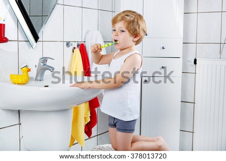 Cute blond kid boy of 2 years learning brushing his teeth in domestic bath. Children learning how to stay healthy. - stock photo