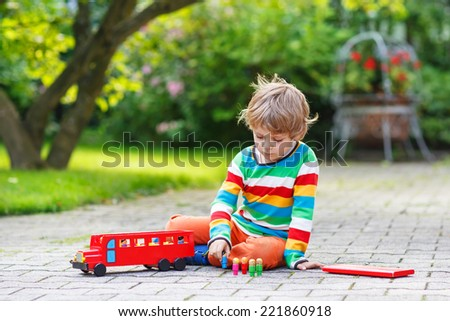 cute blond kid boy playing with red school bus and toys in summer garden.