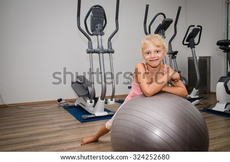 cute blond kid lying over gray ball in the gym and smiling