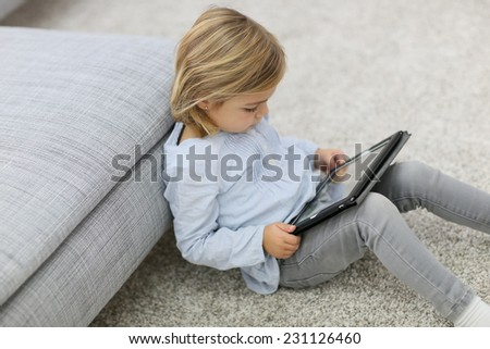 Cute blond little girl watching movie on tablet - stock photo