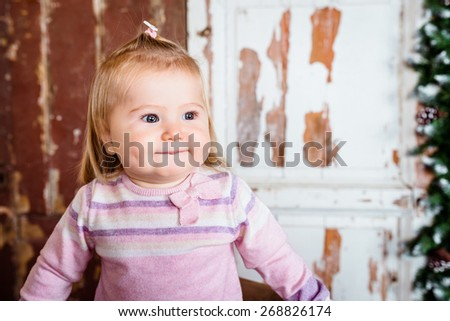 Cute blond little girl with big grey eyes and plump cheeks with pursed lips. Studio portrait on grunge wooden background - stock photo
