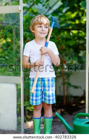 Cute blond little kid boy watering plants and vegetables with can and working with garden hoe in greenhouse. Preschool child helping on sunny summer day. Family, garden, gardening, lifestyle