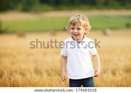 Cute blond little toddler boy of three years playing and having fun on yellow hay field in summer in soft evening light