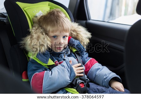 cute blond smiling boy five years sitting in winter jacket with fur in a car in a child car seat to 36 killogramm, buckled and is safe