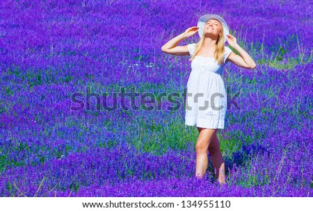 Cute blond teen girl standing on purple lavender meadow, woman wearing white dress and hat take sun bath on floral field - stock photo