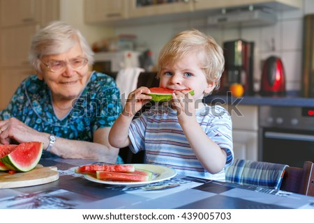 Cute blond toddler boy and his great grandmother eating watermelon in domestic kitchen. Happy family of little kid and retired senior woman enjoying healthy fruit.