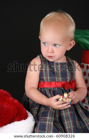 Cute blond toddler holding a christmas decoration in her hands - stock photo