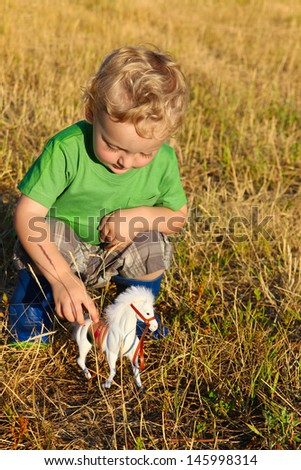Cute blond toddler playing outside in the hay fields - stock photo