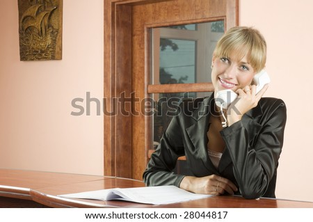 cute blond woman at front desk smiling and talking at phone